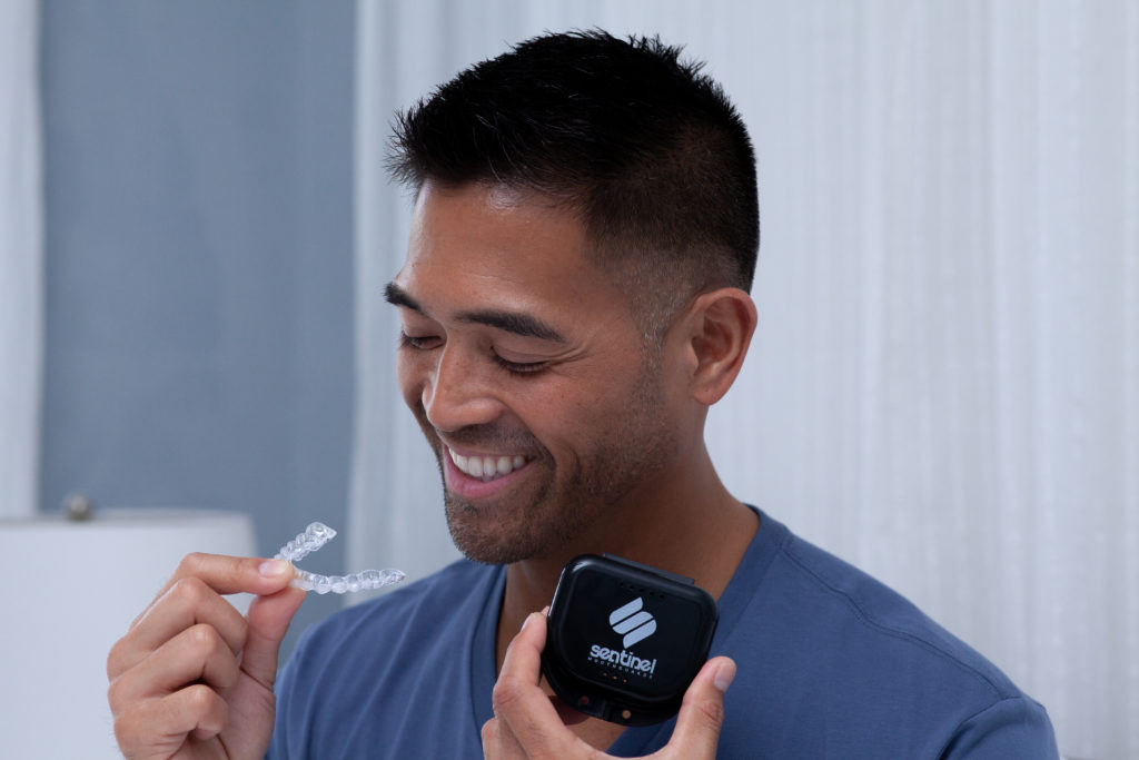 man holding sentinel mouthguard case and night guard